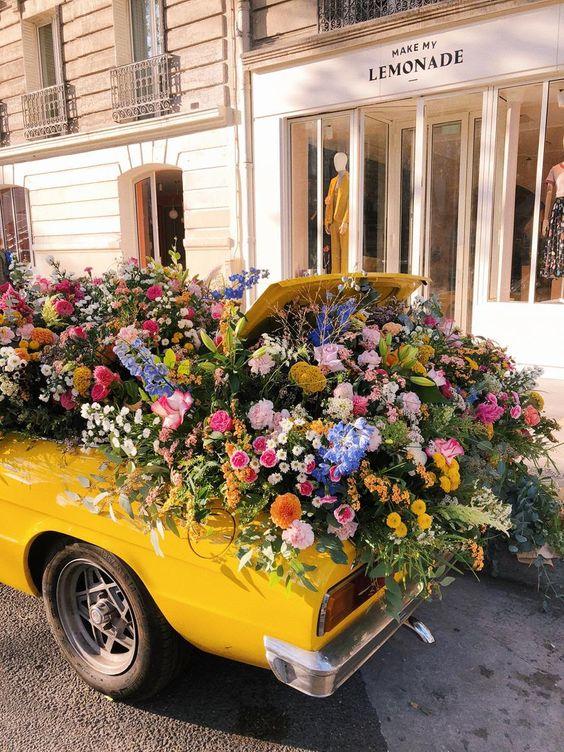 Voiture jaune et coffre rempli de fleurs de printemps
